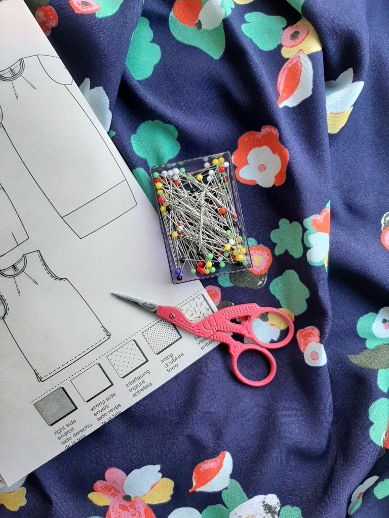 Floral viscose fabric with a Burda sewing pattern, pack of glass-head pins and a pair of pink embroidery scissors