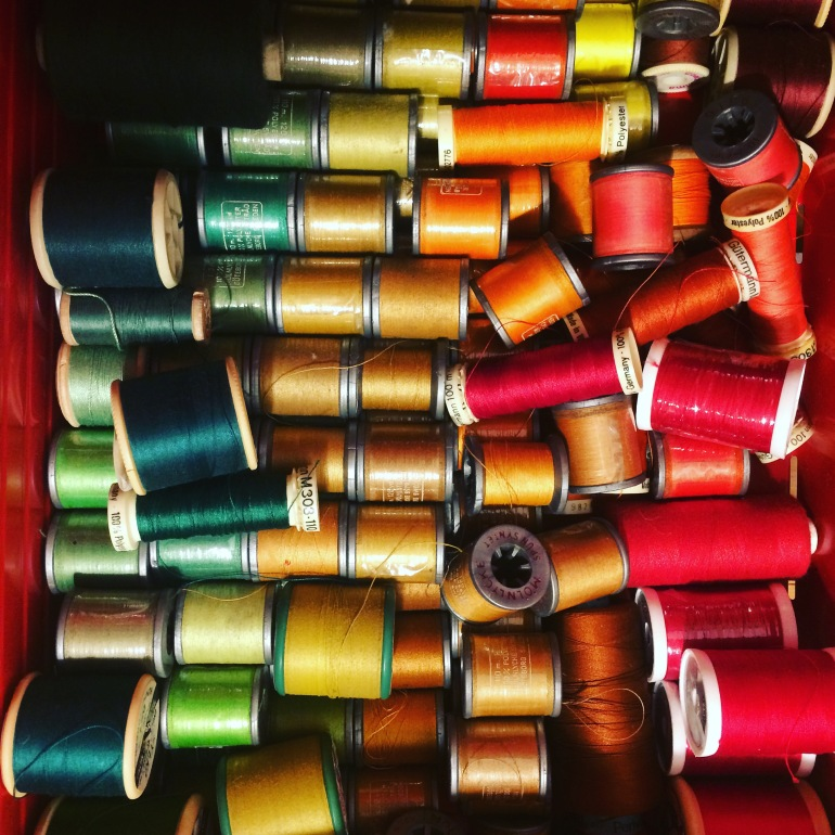Drawer full of reels of sewing thread - green, blue, orange, yellow, red