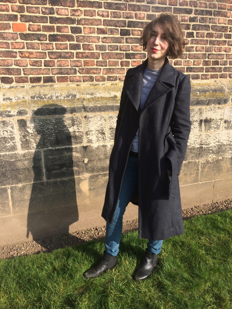 Ruth stands by brick wall wearing grey wool wrap coat made from vintage Maudella pattern