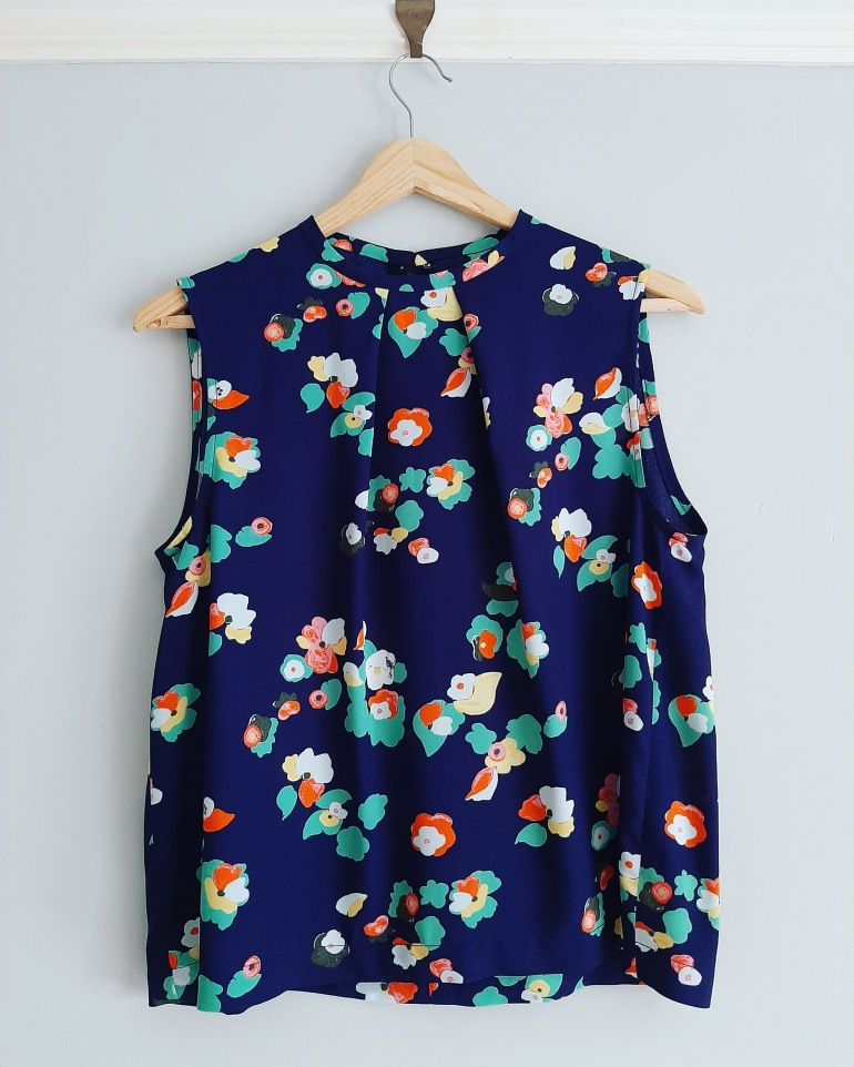 Crew neck sleeveless top with pleated neckline in blue and multicoloured floral viscose fabric hangs on wall