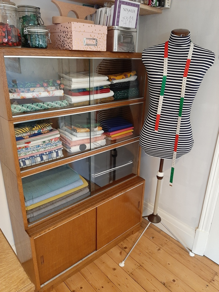 A glass-fronted sewing cabinet repurposed to hold neatly folded fabric stash is in the corner of a room next to a dressmaker's mannequin in a stripe cover with a tape measure hanging from its neck. Above, patterns are stored with a tailor's clapper and kilner jars filled with buttons.