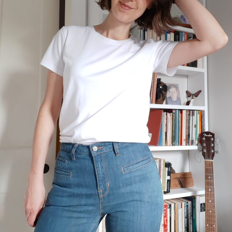 Ruth wear's basic white short-sleeved loose-fit t-shirt tucked into high-waisted jeans. Bookcase and guitar behind.