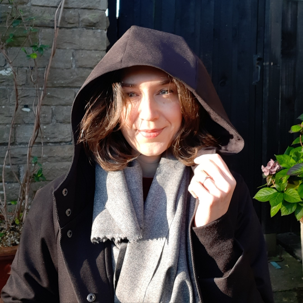 Ruth head and shoulders wearing black Waver Jacket winter parka with hood up and sun catching face. Worn with grey wool scarf.
